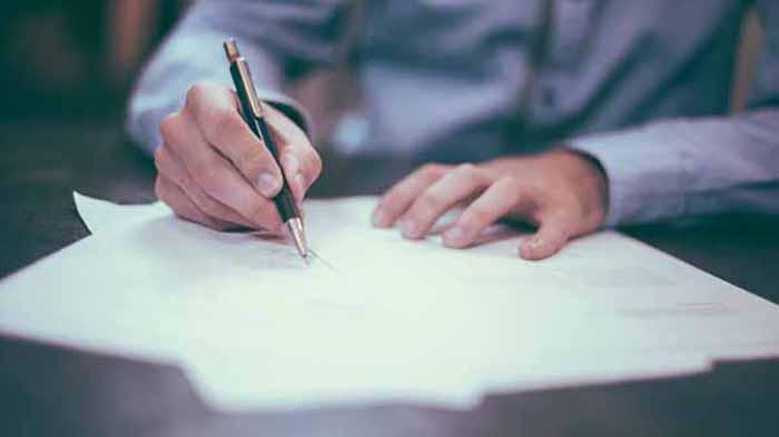 Manos firmando un papel