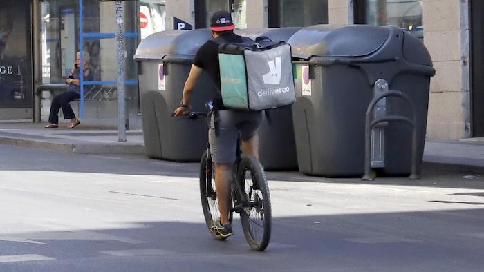 un rider de deliveroo por la calle en la bici