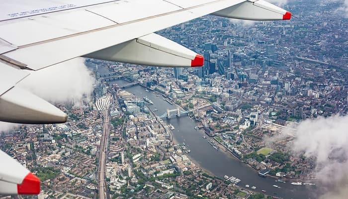 avion entre nubes sobre ciudad. viajes