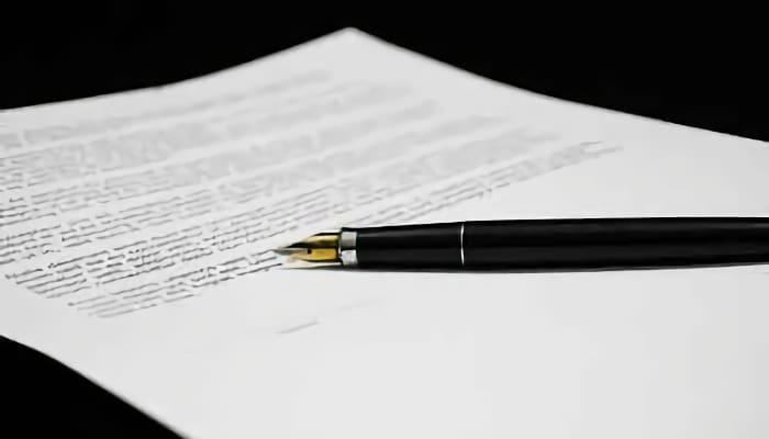 Firma y pluma en un documento. Convenio Colectivo